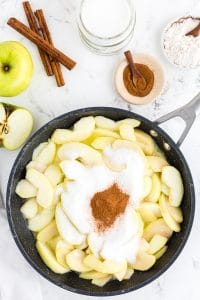 Frying pan with apple slices, sugar and ground cinnamon, bowl with ground cinnamon, cinnamon sticks, bowl with flour, an apple on marble countertop