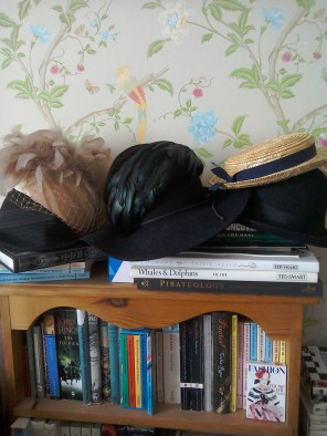 Hats piled up on bookshelf