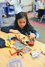 Lower School Student building lego