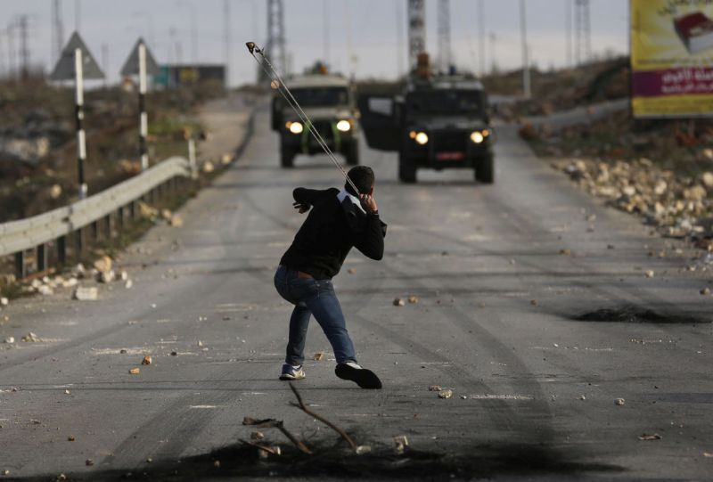 A Palestinian protester uses a sling to throw a stone during clashes with Israeli soldiers in Jalazoun refugee camp near Ramallah