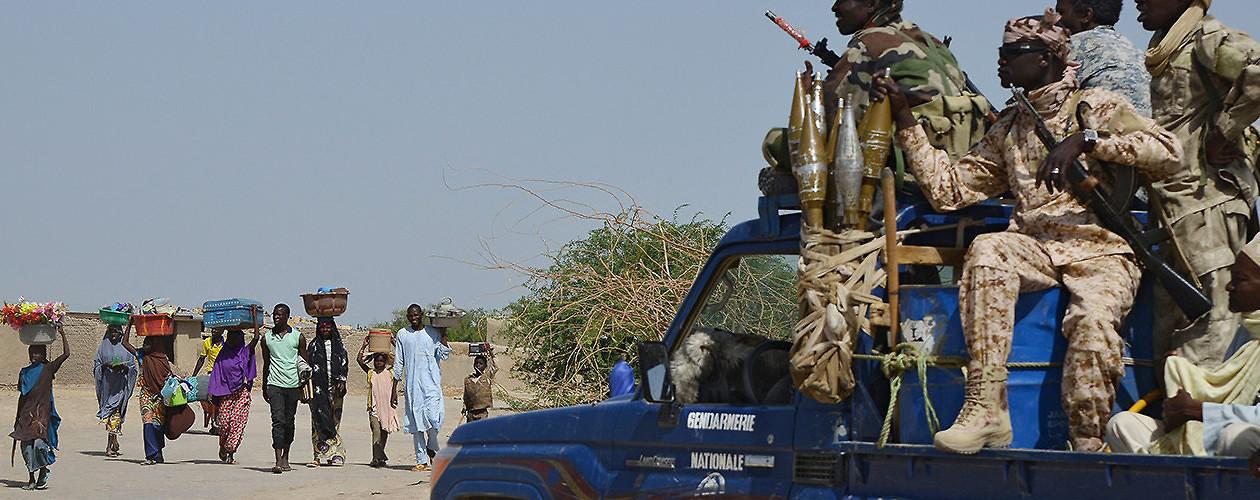 Nigerians fleeing Boko Haram attacks pass Chadian gendarmes near the border of Niger and Chad. Malam Fatori, Nigeria, May 25, 2015. (Issouf Sanogo/AFP/Getty Images)