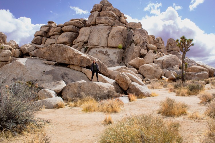 Woman standing atop a boulder grouping at Joshua Tree National Park