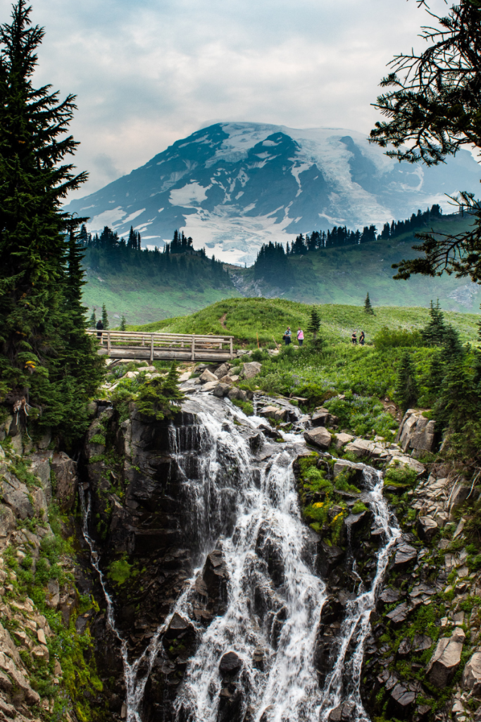 cascading waterfall with a wooden bridge over it and mount rainier in the background