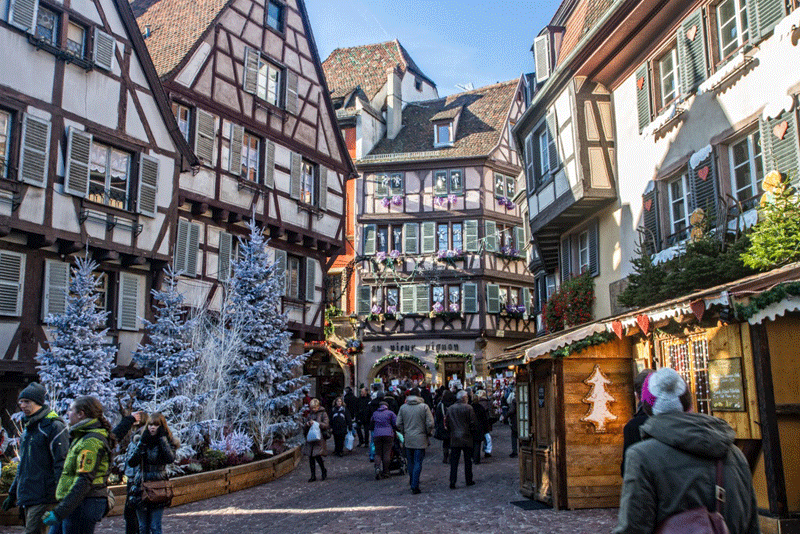 Street in Colmar, Alsace, lined with Christmas trees and wooden chalets selling gifts