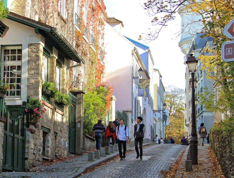 Montmartre, Paris, cobbled street lined with pretty houses that look like a village in the city