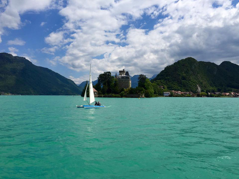 A small sail boat on the vast crystal clear lake of Annecy, Haute-Savoie