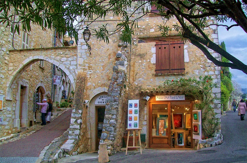 Stone building with shutters on a narrow street lined with art galleries