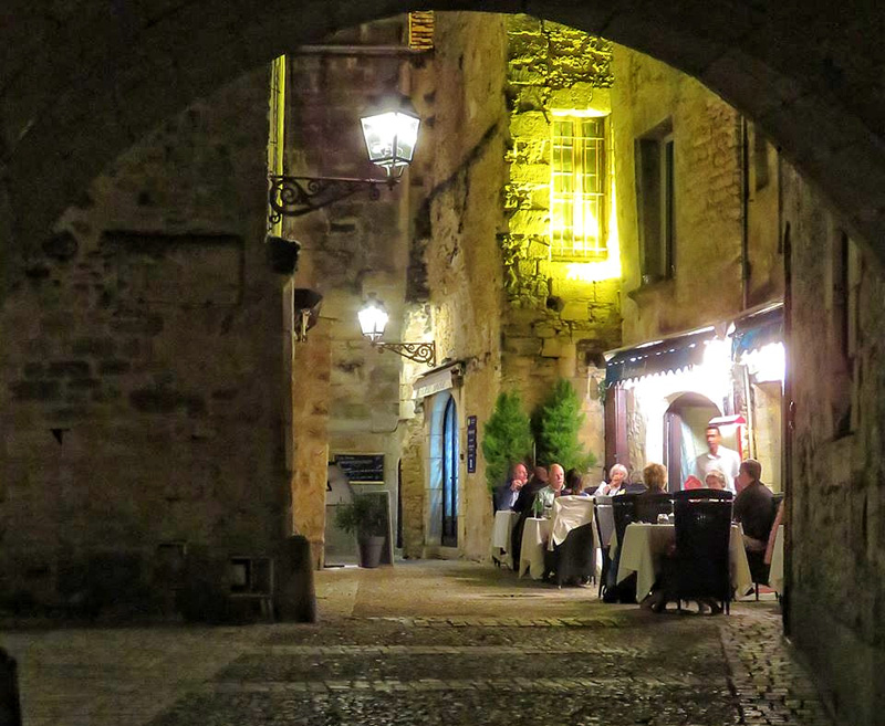 Sarlat town at night, people dining outdoors in a cobbled streets