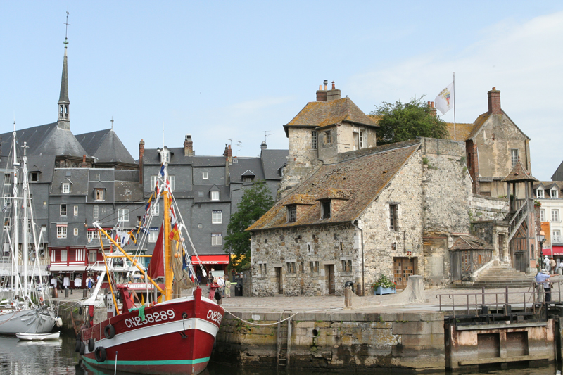 Port town Honfleur, boats in tied up and ancient buildings line the port