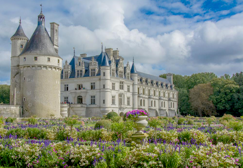 White stone castle with grey slate roof and pointy towers surrounded by blooming colourful flowers