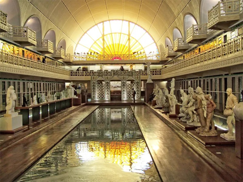 Art deco swimming pool turned museum, statues line the area round the pool and light from a half moon window