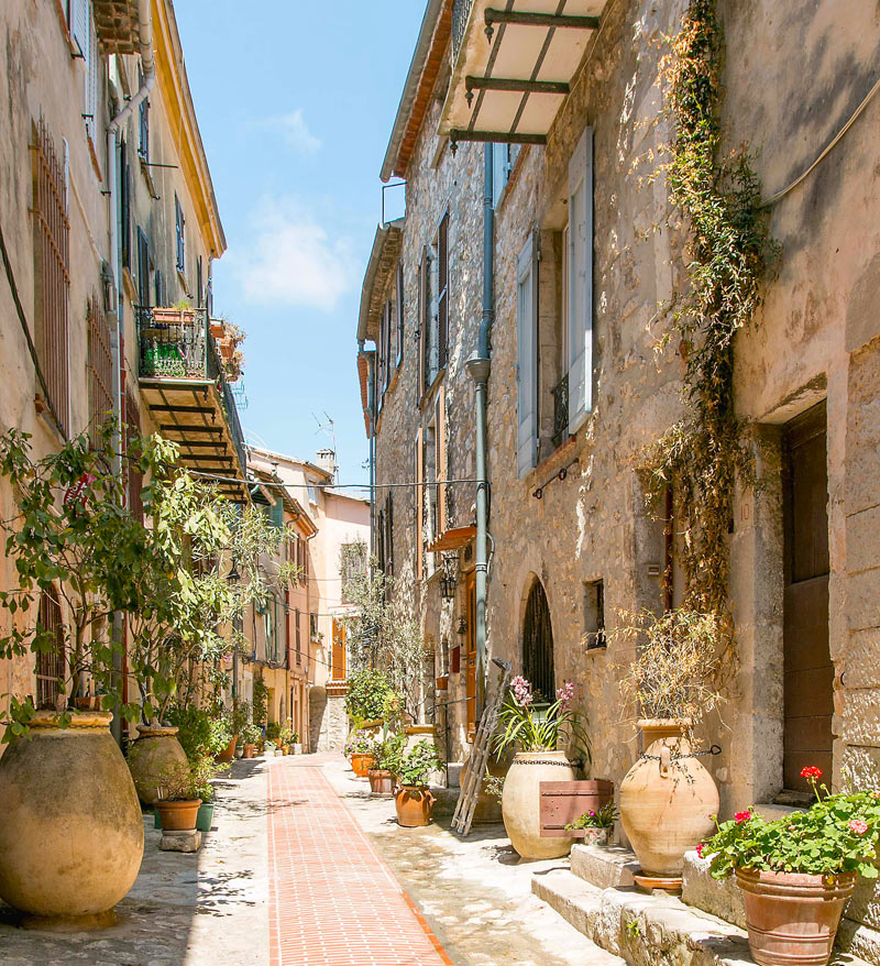 A cobbled street in La Turbie, Provence, scented blooms fill the air