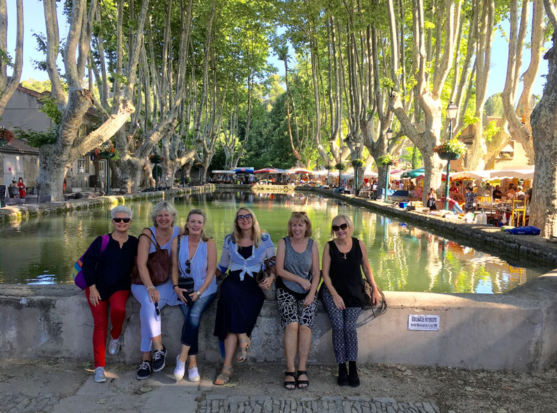 6 women sitting in a beautiful square in Provence, plane trees shade them and a cool pool is behind them