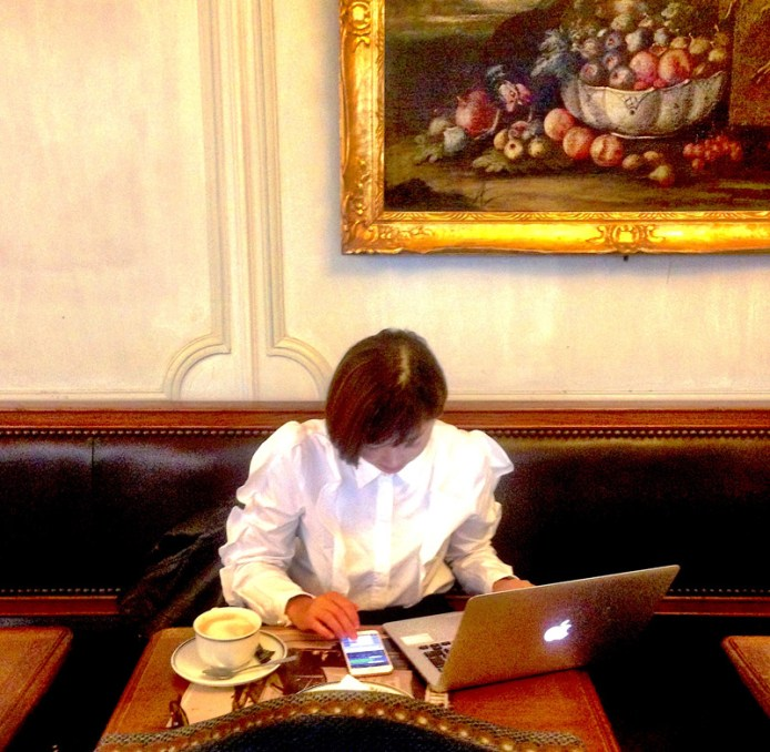 A woman sits in a cafe in Paris using the Wi-Fi