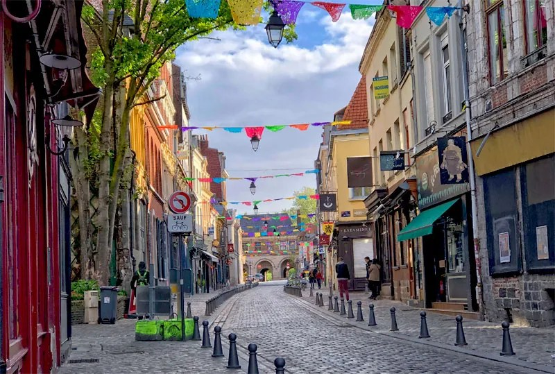 Cobbled street lined with restaurants and shops, bunting hangs across the top, Lille