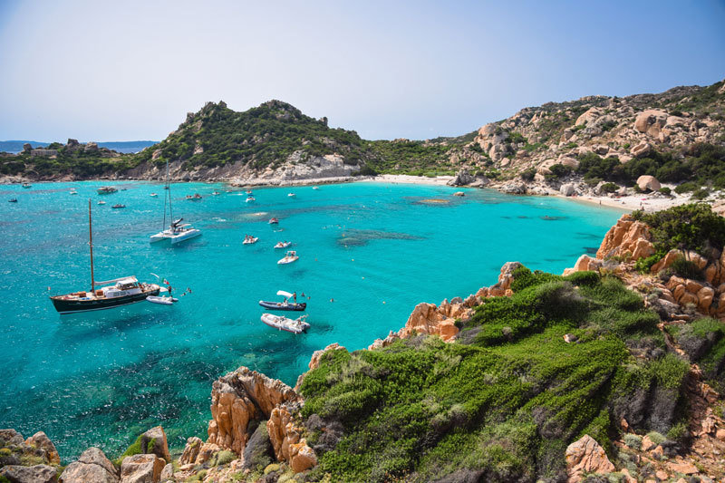 Sail boats in the Mediterranean, calm sea surrounded by rocky landscape