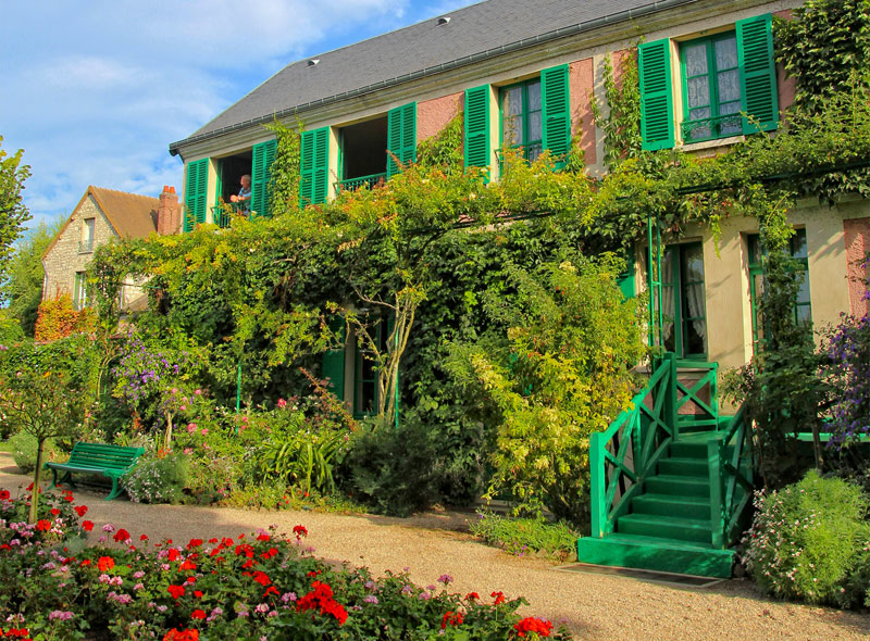 Man stands at window of Claude Monet's house in Giverny overlooking the gardens