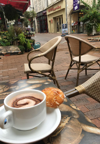 Cup of coffee on a table of a terraced cafe in a cobbled street in old town Saintes, Charentes