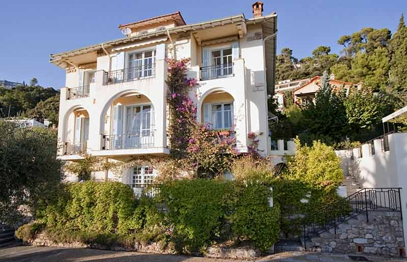 Large villa covered in blooming pink flowers and vines in Grasse, southern France