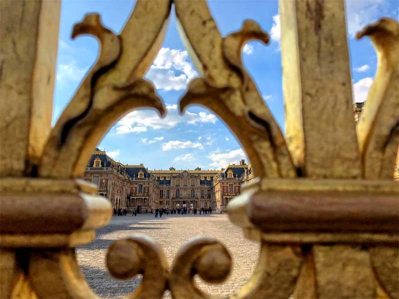 Chateau de Versailles viewed through a golden gate