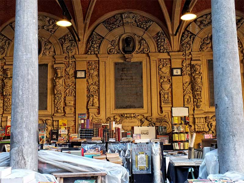 Ancient arcade with second hand book stalls spread out in Lille old town