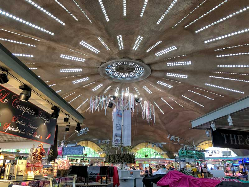 Inside Royan central market, a concrete building with hundreds of tiny windows set in the round roof