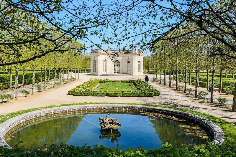 View of Marie Antoinette's garden at the Chateau of Versailles, a pretty pond and formal hedges
