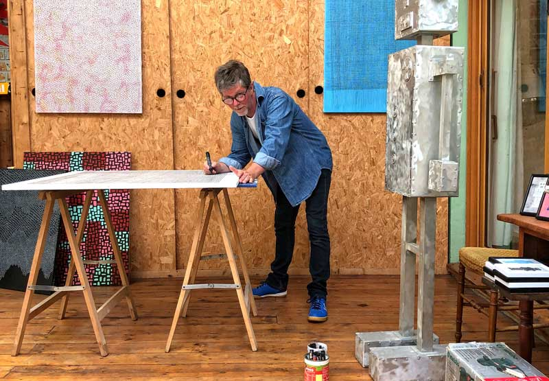Artist at work in a studio in Le Havre leaning over a workbench, art on the walls