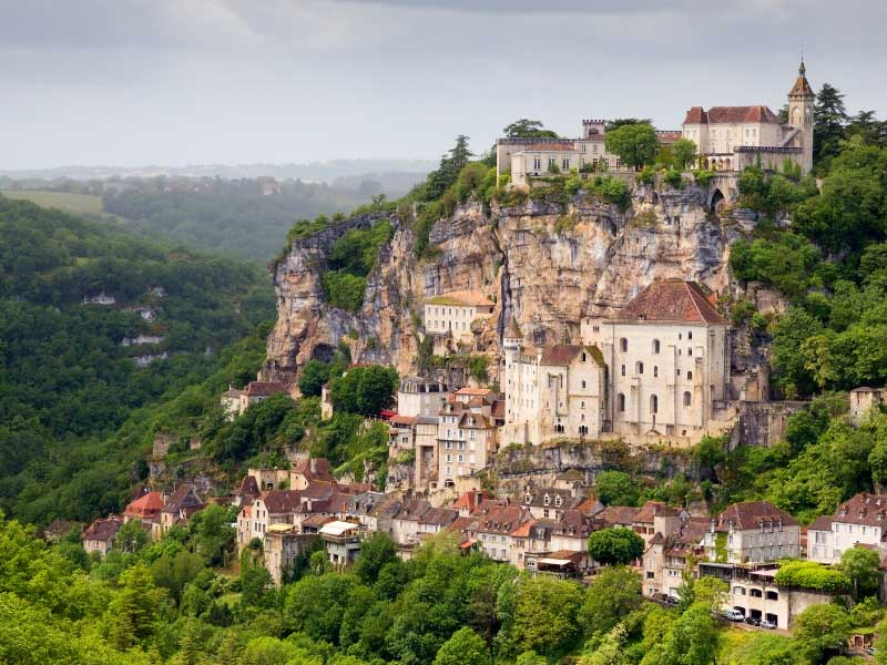 View of the town of Rocamadour, built into and on top of a cliff and surrounded by forest