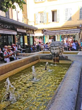 Tables laid around a sprinkling fountain in Carpentras