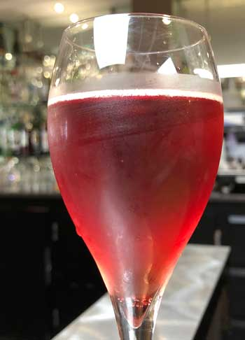 Glass of sparkling red liquid - a Kir Normand