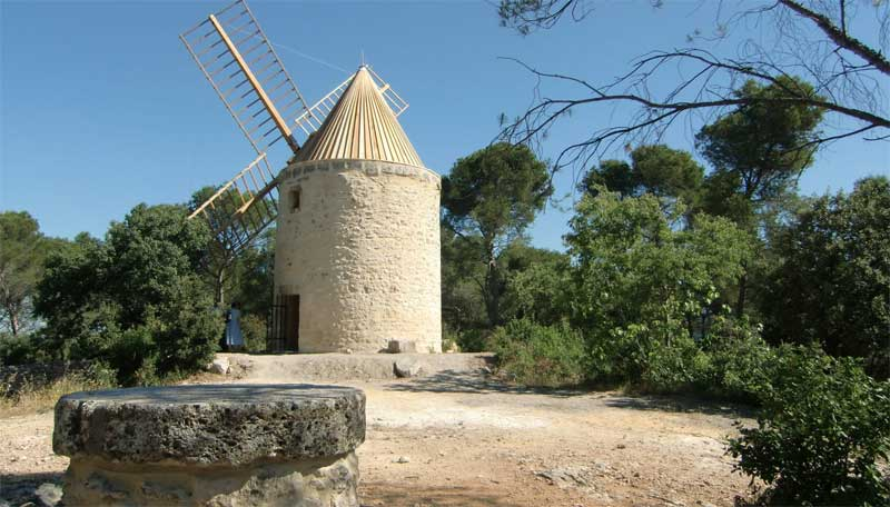 White stone windmill against a deep blue sky in Fontvielle, France