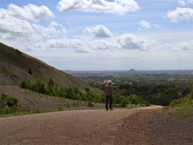 Man walks up a coal slag heap to admire the views over Lens. northern France