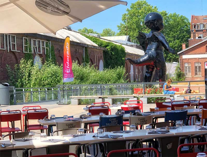 Tables and chairs on a terrace overlooking a giant tailed baby sculpture in Lille