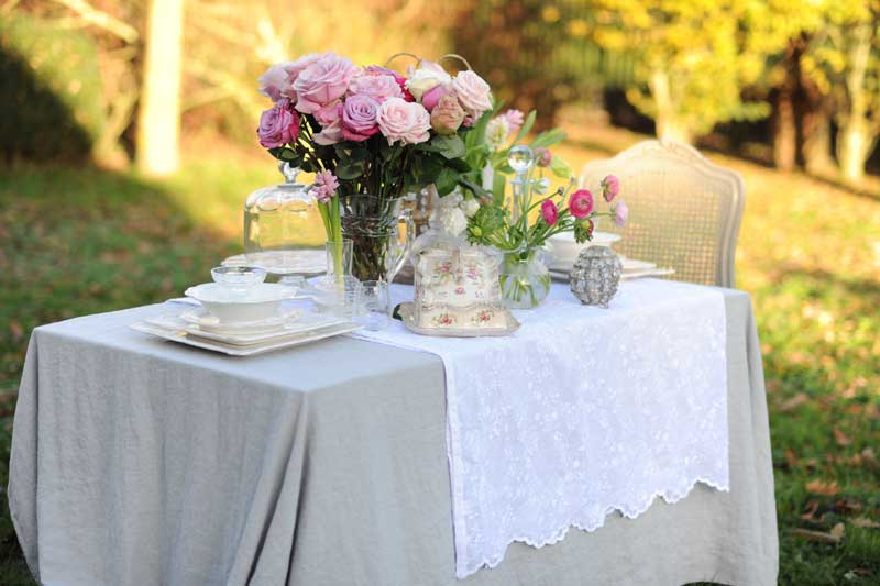 Table laid with beautiful table cloths, bunches of flowers and pretty ornaments