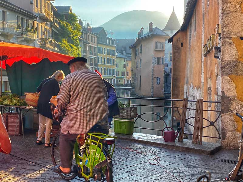 Annecy market on a sunny day, beret-wearing man on bike crosses a cobbled bridge