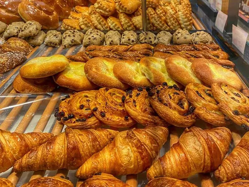 Window of a boulangerie in France filled with croissants and pastries