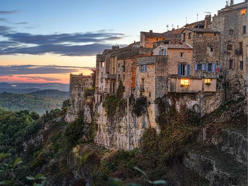 The perched village of Tourrettes-sur-Loup clinging to a cliff, house lights glow at dusk