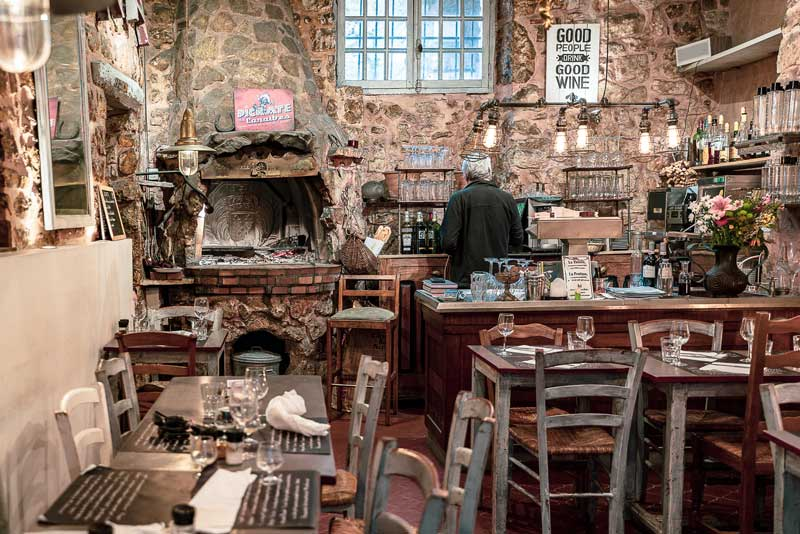 Dining room of a rustic style restaurant with stone walls and wooden chairs and tables