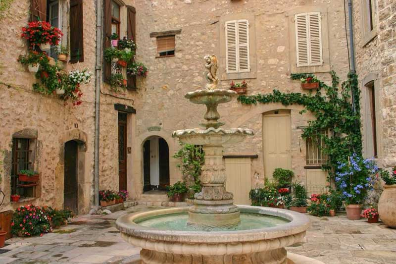 Pretty square with a fountain in the middle surrounded by ancient stone houses