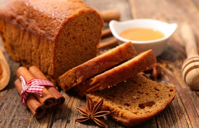 Gingerbread loaf on a wooden board with bowl of honey and some spices