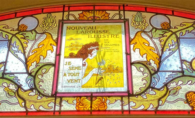 Stained glass window depicting a woman blowing seeds from a dandelion flower