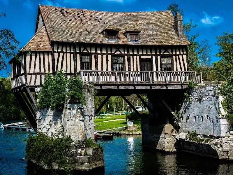 Pretty half timbered house on a bridge over a river in Normandy