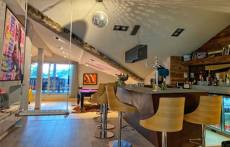 Indoor swing in a large room in a chalet, disco ball, bar and art on the walls, Les Gets