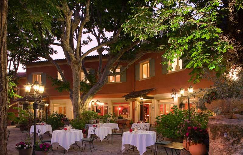 Tables laid for dinner under trees on a sunny terrace, les Florets, Gigondas, Provence