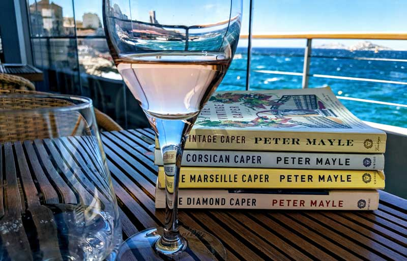 Peter Mayle Caper Series books on a table at a restaurant overlooking the Med in Marseille