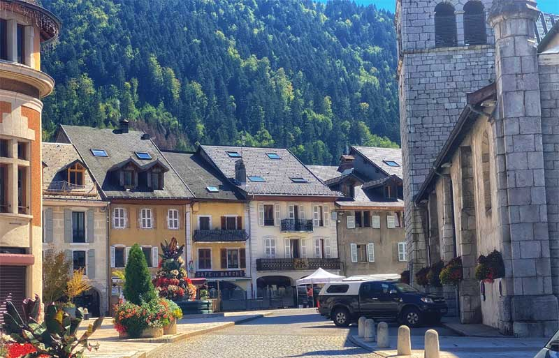 Street view of Thones in the French Alps, traditional cafe and village church in the centre