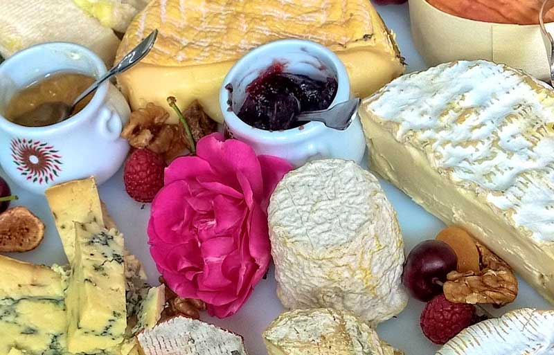 Cheese on a tray with roses and jams