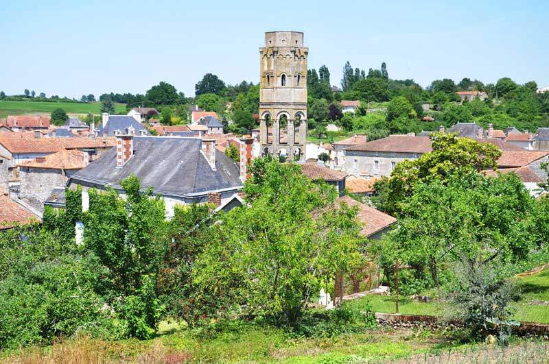 Village surrounded by trees and countryside with a tall ancient tower sticking up over tiled roofs
