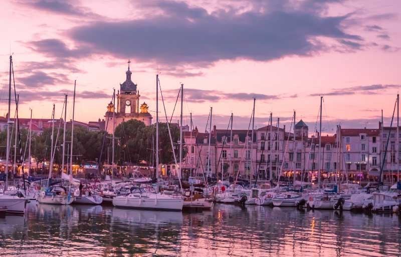 La Rochelle at dusk, clouds tinged pink over the old city